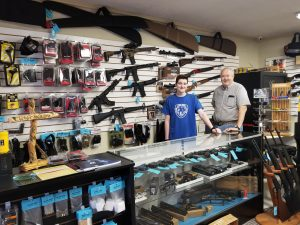 Paul Barnes, right, and his son, Michael, invite customers to their new gun shop in LaGrange