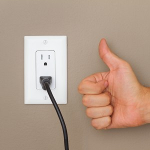 Thumbs up, and Electric cable in Electrical Outlet on the Wall. Power 110v