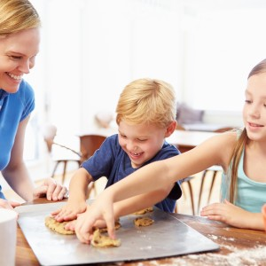 Mother And Children Baking Cookies Together At Home