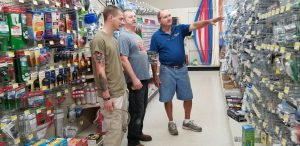 Short and Paulk's Deker Hixon, right, assists customers Chandler Buchanan and his dad, Don.
